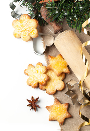 Top view on homemade sugar cookies served with metal cookie cutters and wooden rolling pin near christmas tree over white photo