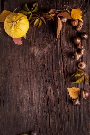 Ornament met pompoen, eikels en herfstbladeren op oud hout als achtergrond Stockfoto