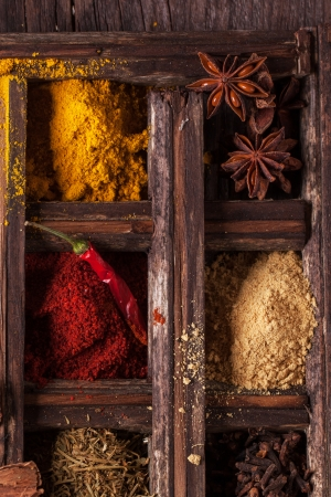Mix of spices in old wooden box photo