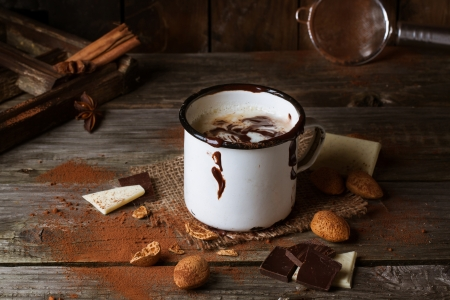 hot chocolate drink: Vintage mug with hot chocolate served with chunks of white and dark chocolate and almonds on old wooden table