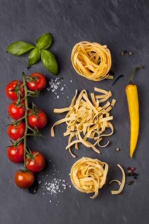 Top view on dry pasta, fresh tomatoes, yellow chili pepper and basil served with sea salt on dark gray background