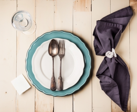 plate of food: Top view on table setting with vintage silverware on white and turquoise plates with blank guest card on white wooden table