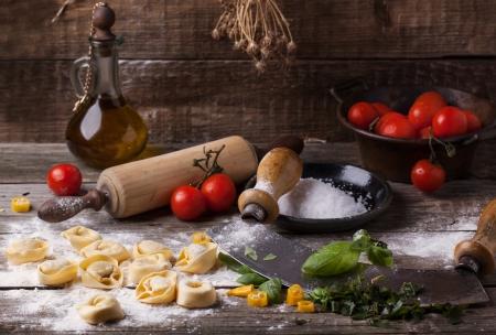 밀가루, 바질, 토마토, 올리브 오일, 빈티지 주방 액세서리와 함께 오래 된 나무 테이블에 만든 파스타 라비올리