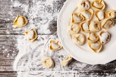 carbohydrates food: Top view on plate of homemade pasta ravioli over wooden table with flour