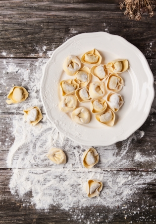 Top view on plate of homemade pasta ravioli over wooden table with flour photo