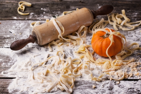 Raw homemade pasta with pumpkin, flour and vintage rolling pin over old wooden table photo