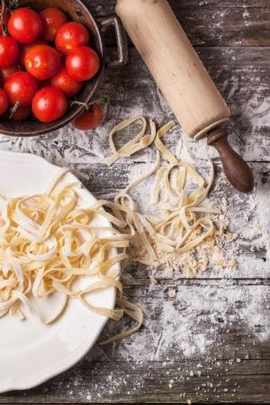 Bovenaanzicht op Ruwe zelfgemaakte pasta met tomaten en bloem over oude houten tafel