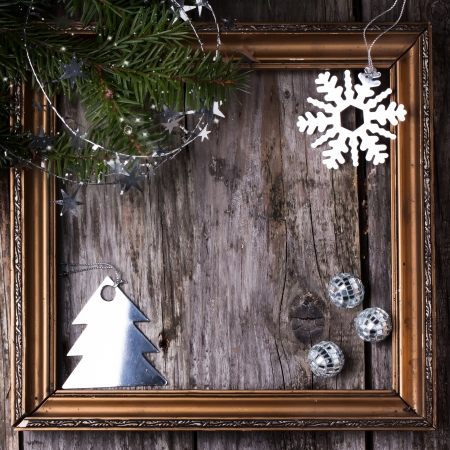 Christmas card with gold frame, decorated with silver toys and christmas tree over old wooden background photo