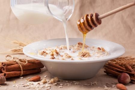 Placa de muesli com leite derramando e mel, canela e nozes sobre o fundo de mat Imagens