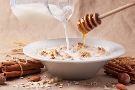 Plate of muesli with pouring milk and honey, cinnamon and nuts over textile background