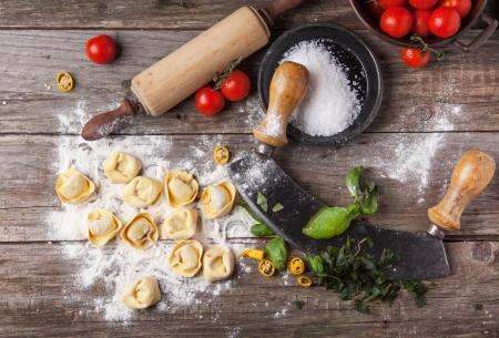 Vista superior de raviolis de pasta casera en tabla de madera con la harina, albahaca, tomates y accesorios de cocina de época Foto de archivo