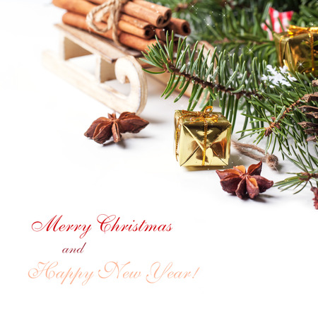 Christmas card with wooden sled with heap of cinnamon and golden gift box over white with sample text photo
