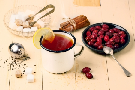 stimulated: Vintage white mug of tea with lemon and briar berries, served with tea strainer and sugar cubes over white wooden table. See series