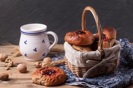Basket of homemade buns with jam, served on old wooden table with walnuts and cup of milk. See series photo