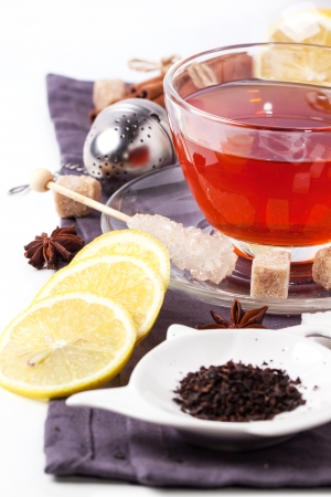 Cup of tea with lemon and spices, served with tea strainer over white. See sries photo