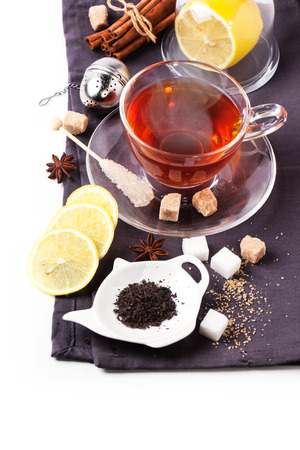 stimulated: Cup of tea with lemon and spices, served with tea strainer over white. See sries Stock Photo