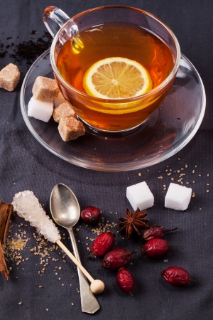 stimulated: Glass cup of tea with sugar cubes, berries and spices, served over dark gray textile Stock Photo