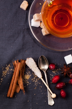 stimulated: Top view on cup of tea with sugar cubes, berries and spices, served over dark gray textile