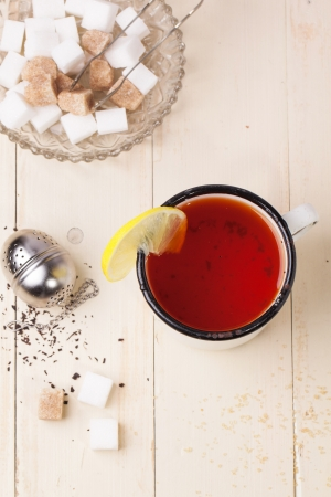 stimulated: Top view on vintage white mug of tea with lemon, served with tea strainer and sugar cubes over white wooden table
