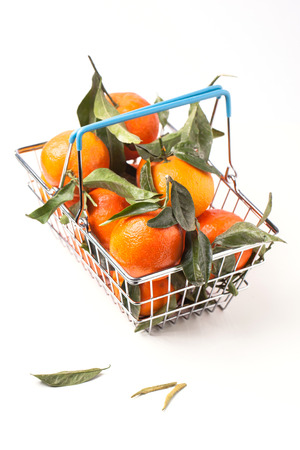 Metal food basket full of tangerines with leaves isolated over white photo