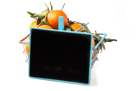 Metal food basket full of tangerines with leaves and empty chalkboard isolated over white photo