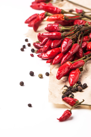 Bundles of red hot chili peppers with peppercorns on crumpled paper over white