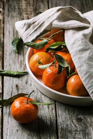 Plaat van mandarijnen met bladeren op oude houten. Zie serie