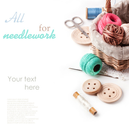 Basket of threads with wooden buttons and scissors over white with sample text