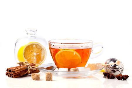 stimulated: Cup of tea with lemon and spices, served with tea strainer isolated over white. See series