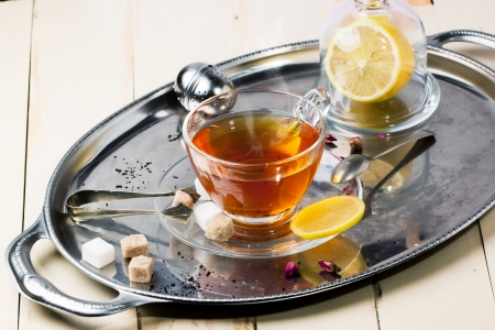 stimulated: Glass cup of tea with sugar cubes, lemon and dry rose buds, served on silver vintage tray on white wooden table. See series Stock Photo
