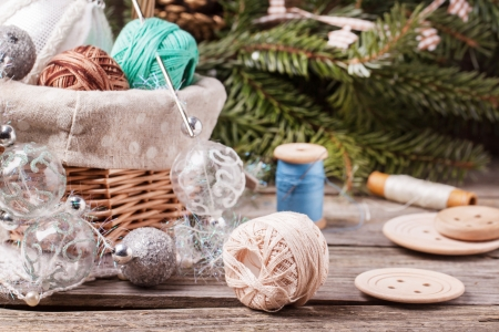 Basket of christmas toys with ball of threads and buttons over Christmas tree on wooden background photo