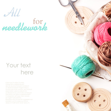 Basket of threads with wooden buttons and scissors over white with sample text photo