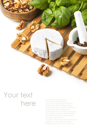 Cheese Camembert, walnuts and fresh basil served on wooden board over white with sample text photo