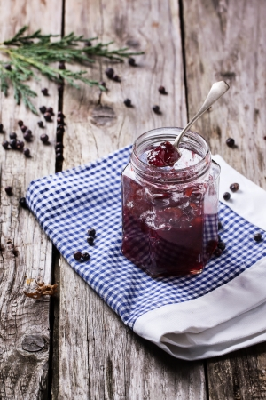 preserving: Jar of plum and juniper jam on old wooden table Stock Photo