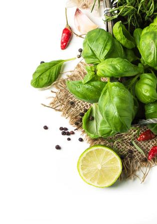 Bovenaanzicht op bosje verse kruiden basilicum en rozemarijn met peper en limoen op zak over wit
