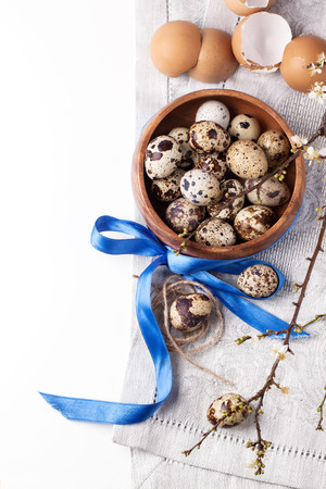 Top view on wooden bowl of quail eggs with blossom branch and eggs shell over white photo