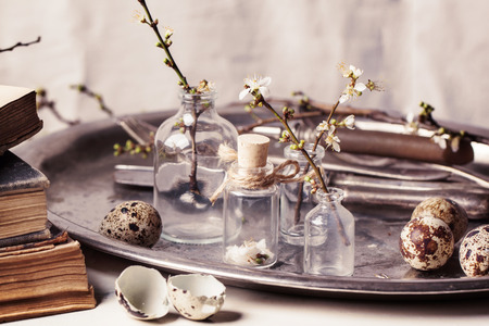 Fragment of Easter interior with little glass vials, blossom branch and quail eggs. See series photo