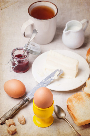 Breakfast with eggs and toasts served with jam and butter over white textile with vintage texture. See series. photo