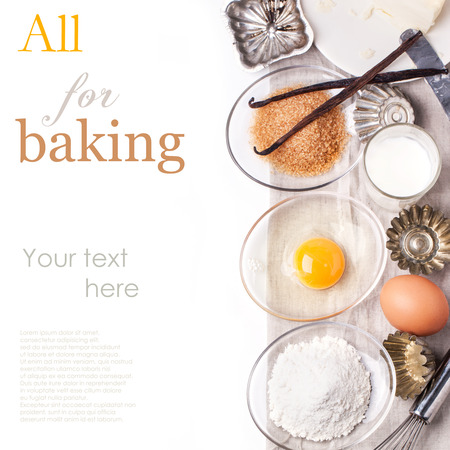 Top view on ingredients for baking (flour, egg, brown sugar) with vintage cupcakes forms over white with sample text photo