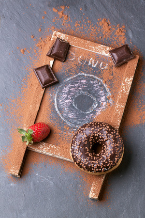 Top view on chocolate and drawing donuts with fresh strawberries and dark chocolate served on chalkboard over black stone table. See series photo