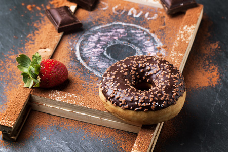 Chocolate and drawing donuts with fresh strawberries and dark chocolate served on chalkboard over black stone table. See series photo