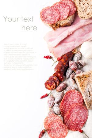 Set di prosciutto e salame salsicce servito con pane fresco, aglio e red hot chili peppers su bianco con testo di esempio Archivio Fotografico