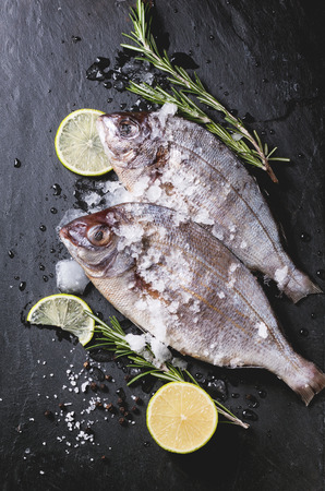 Top view on tow raw fish bream with rosemary, lime and ice over black stone background. photo