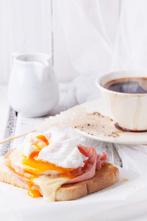 Breakfast with cup of coffee and toast with cheese and poached egg served on white wooden table photo