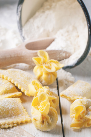 perle: Close up of homemade pasta ravioli and perle on wooden table with metal mug of flour. See series Stock Photo