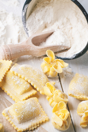 perle: Homemade pasta ravioli and perle on wooden table with metal mug of flour