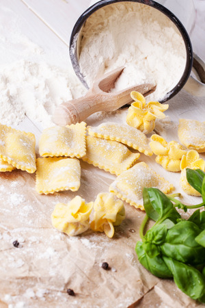 perle: Homemade pasta ravioli and perle on white wooden table with vintage mug of flour and fresh basil. See series