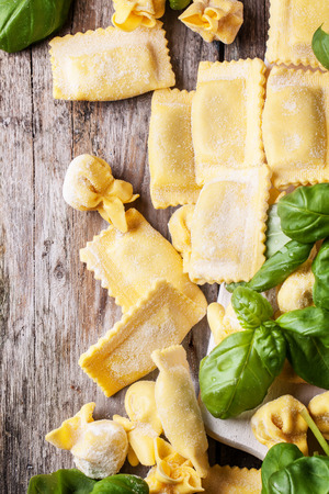 perle: Top view on homemade pasta ravioli and perle on old wooden table with fresh basil Stock Photo