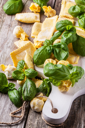 perle: Homemade pasta ravioli and perle on old wooden table with fresh basil
