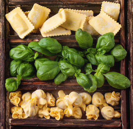 perle: Top view on wooden box with homemade pasta ravioli and perle with fresh basil on old wooden table.